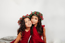 Two sisters in holly headpieces pose for christmas photo