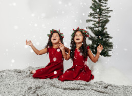 Two children dressed in christmas outfits play in snow