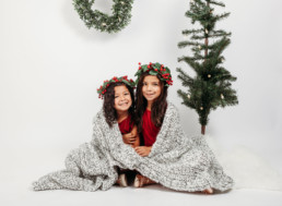 Two children snuggle under blanket in holiday photo