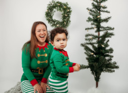 Toddler and mother gather around christmas tree for holiday photo