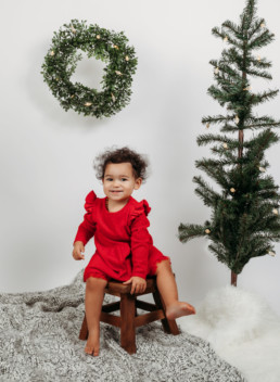 Toddler poses for holiday photo near christmas tree