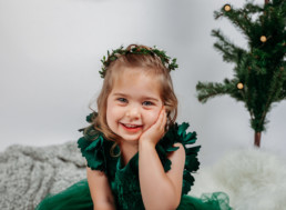 Toddler in green dress poses for holiday photograph