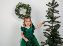 Toddler touching a christmas tree and smiling in photograph