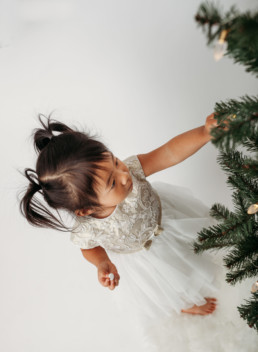 Young child touches christmas tree in studio photo