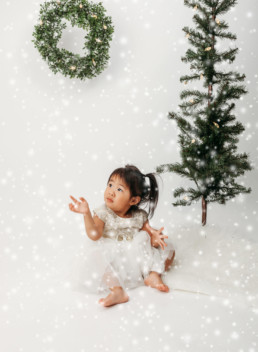 Toddler poses in snow for christmas themed photo