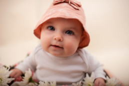 Baby sits for in studio photo shoot in Pasadena, California in a bucket of flowers