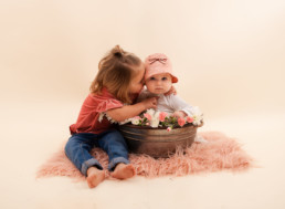 Sisters sit for in studio photo shoot in Pasadena, California with a bucket of flowers for Valentine's day session