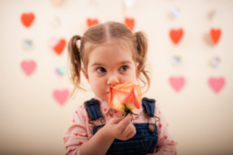 Toddler sits for in studio photo shoot in Pasadena, California with valentine day themed props, roses