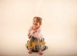 Toddler in studio photo shoot in Pasadena, California with valentine day themed props, love sign