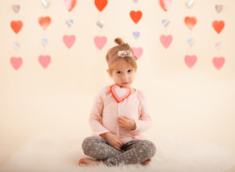 Toddler in studio photo shoot in Pasadena, California with valentine day themed props, heart backdrop