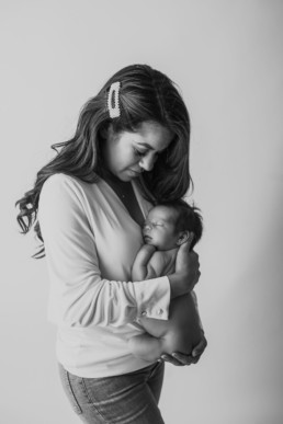 Mother and baby cuddle during newborn photo shoot in studio