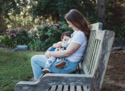 Mother and toddler breastfeed while sitting on a bench in the garden